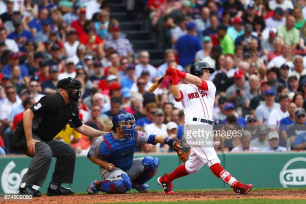 Andrew Benintendi of the Boston Red Sox hits a home run against the Chicago Cubs during the fifth inning at Fenway Park on April 29 2017 in Boston...
