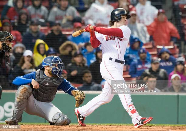 Andrew Benintendi of the Boston Red Sox hits an RBI single against the Texas Rangers in the first inning at Fenway Park on May 25 2017 in Boston...