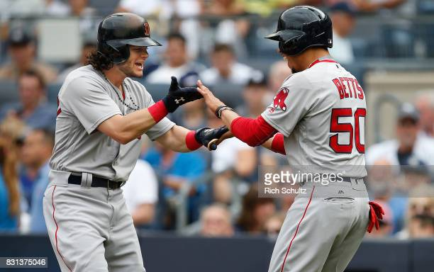 Andrew Benintendi of the Boston Red Sox is congratulated by Mookie Betts after hitting a three home run against the New York Yankees during the third...