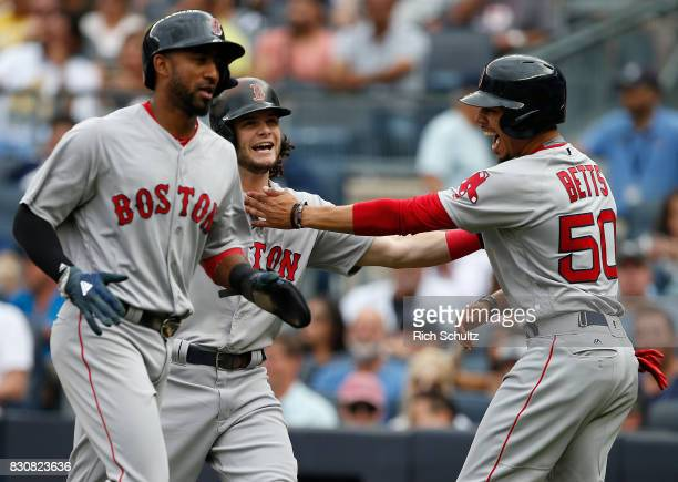 Andrew Benintendi of the Boston Red Sox is congratulated by teammates Eduardo Nunez and Mookie Betts after all three scored on Benintendi's three...