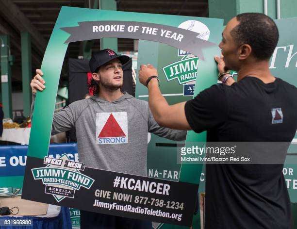 Andrew Benintendi of the Boston Red Sox is handed a 'Rookie of the Year' prop by Mookie Betts before going on air at the Jimmy Fund Radio Telethon...