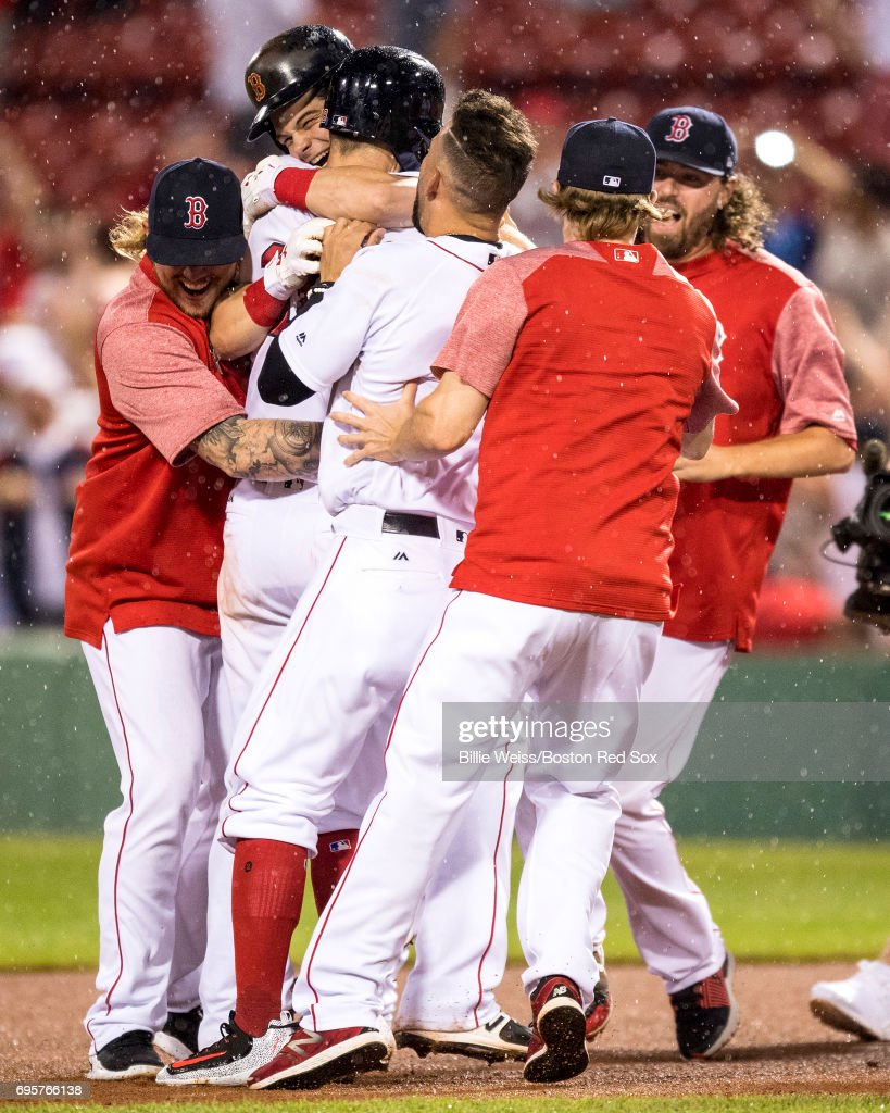 Andrew Benintendi #16 of the Boston Red Sox is mobbed by teammates after hitting a walk-off double to end the game against the Philadelphia Phillies on June 13, 2017 at Fenway Park in Boston, Massachusetts.