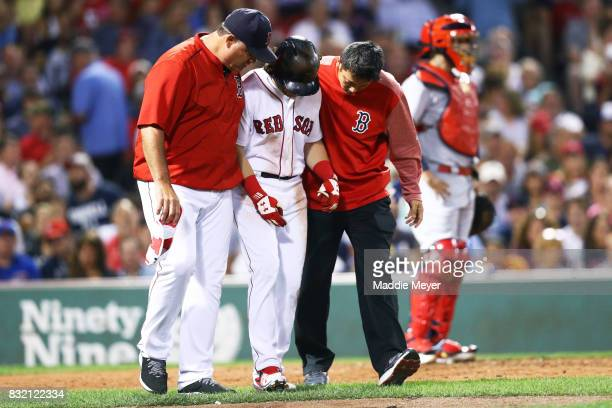 Andrew Benintendi of the Boston Red Sox is tended to after being struck by a pitch during the fifth inning against the St Louis Cardinals at Fenway...