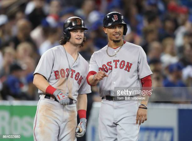 Andrew Benintendi of the Boston Red Sox meets with Mookie Betts at third base during a pitching change in the seventh inning during MLB game action...