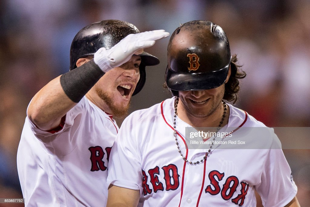 Andrew Benintendi #16 of the Boston Red Sox reacts with Christian Vazquez #7 after hitting a pinch hit solo home run during the ninth inning of a game against the Toronto Blue Jays on September 25, 2017 at Fenway Park in Boston, Massachusetts.