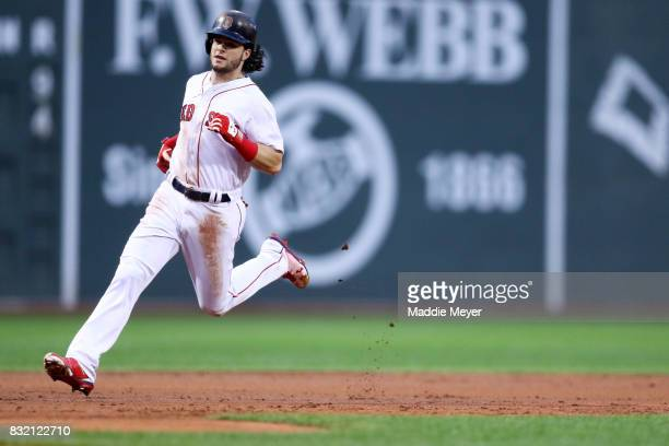Andrew Benintendi of the Boston Red Sox rounds third base during the first inning against the St Louis Cardinals at Fenway Park on August 15 2017 in...