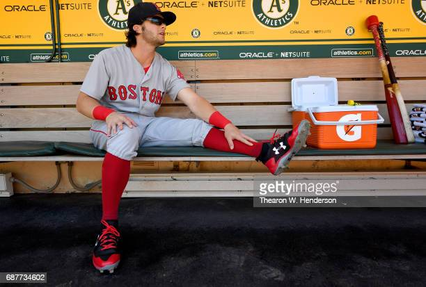 Andrew Benintendi of the Boston Red Sox stretches in the dugout prior to the start of his game against the Oakland Athletics at Oakland Alameda...