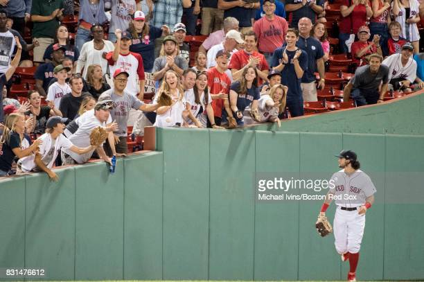 Andrew Benintendi of the Boston Red Sox tosses a ball to fans during the eighth inning of a game against the Cleveland Indians on August 14 2017 at...