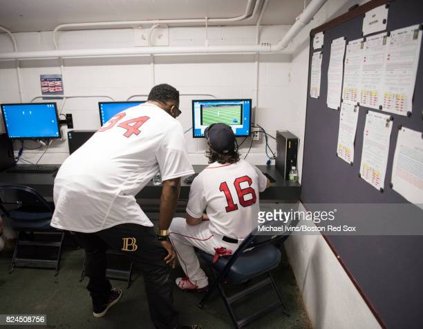 Andrew Benintendi of the Boston Red Sox watches film with former Red Sox David Ortiz before a game against the Kansas City Royals in the first inning...
