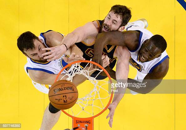 Andrew Bogut and Draymond Green of the Golden State Warriors battle for a rebound against Kevin Love of the Cleveland Cavaliers in Game 1 of the 2016...