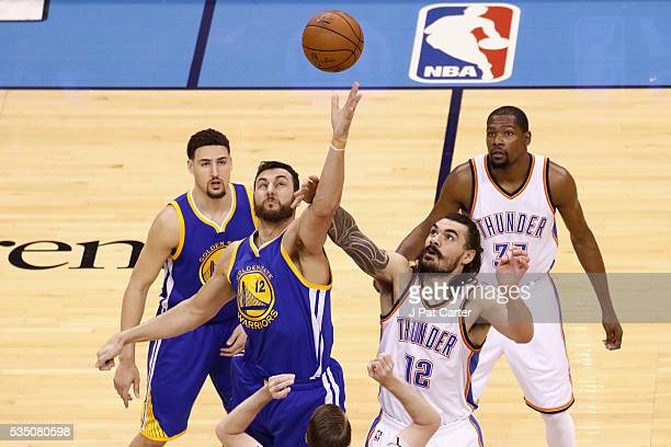 Andrew Bogut of the Golden State Warriors and Steven Adams of the Oklahoma City Thunder battle for the opening tipoff in game six of the Western...