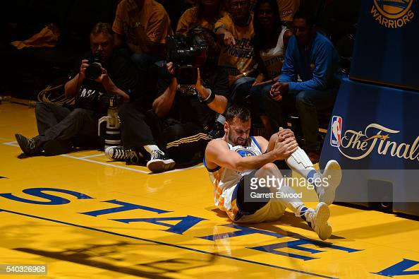 Andrew Bogut of the Golden State Warriors grabs his knee in pain during Game Five of the 2016 NBA Finals against the Cleveland Cavaliers on June 13...
