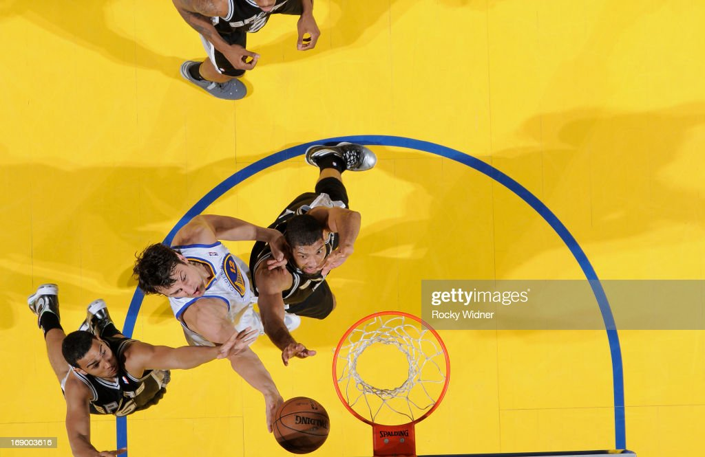 Andrew Bogut #12 of the Golden State Warriors rebounds against Cory Joseph #5 and Tim Duncan #21 of the San Antonio Spurs in Game Four of the Western Conference Semifinals during the 2013 NBA Playoffs on May 12, 2013 at Oracle Arena in Oakland, California.