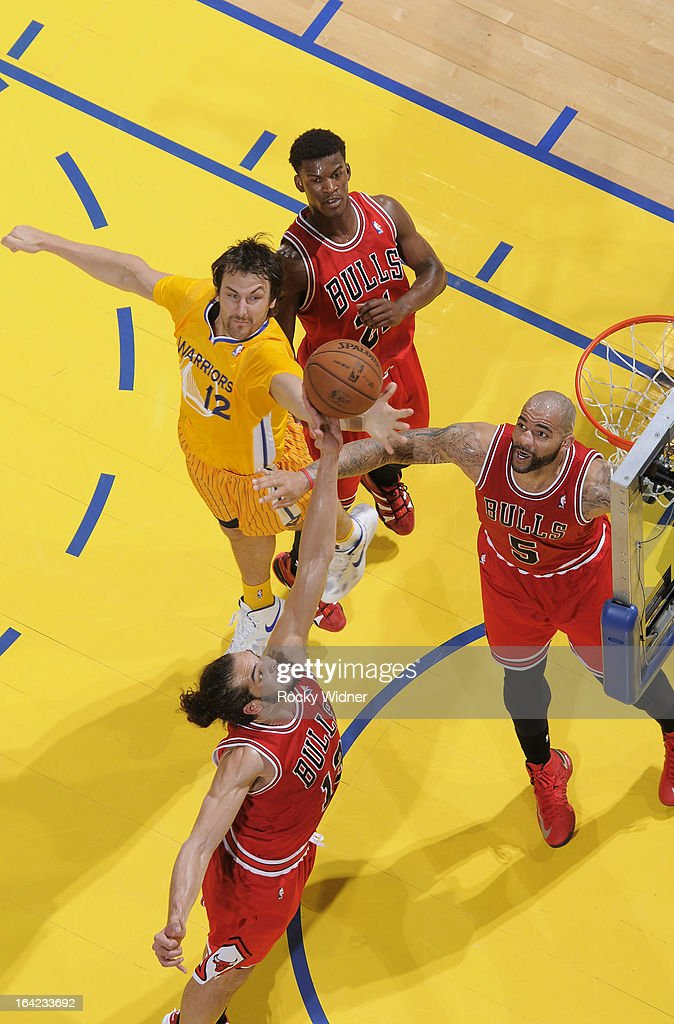 Andrew Bogut #12 of the Golden State Warriors rebounds against Joakim Noah #13 and Carlos Boozer #5 of the Chicago Bulls on March 15, 2013 at Oracle Arena in Oakland, California.