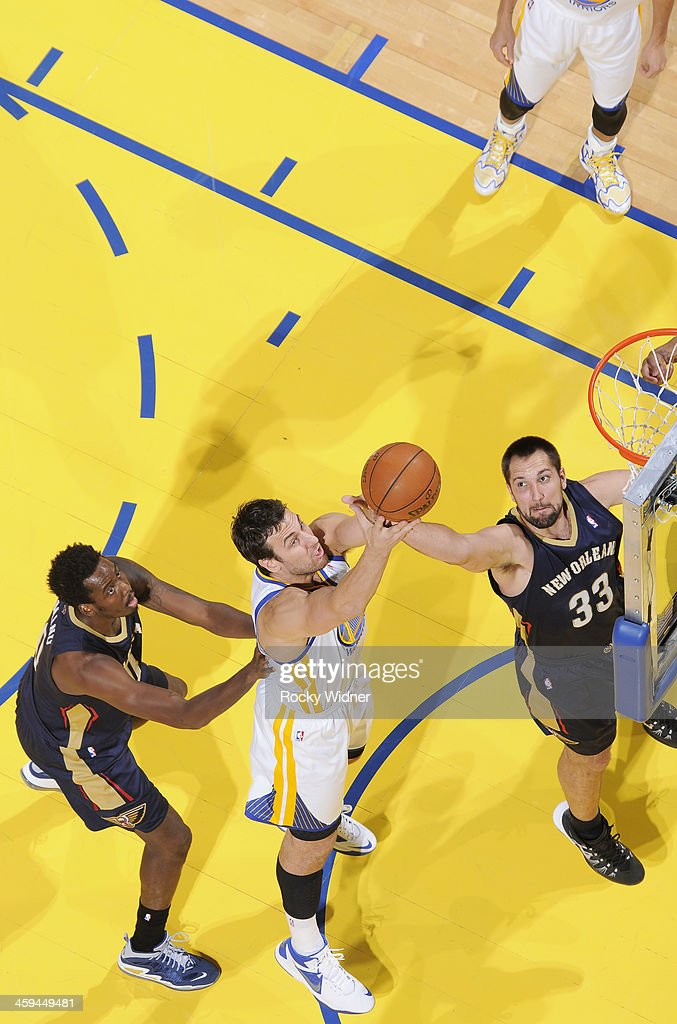Andrew Bogut #12 of the Golden State Warriors rebounds against Ryan Anderson #33 and Al-Farouq Aminu #0 of the New Orleans Pelicans on December 17, 2013 at Oracle Arena in Oakland, California.