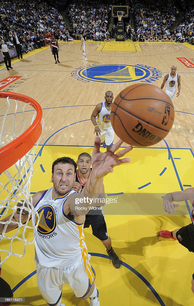 Andrew Bogut #12 of the Golden State Warriors rebounds against the Portland Trail Blazers on March 30, 2013 at Oracle Arena in Oakland, California.