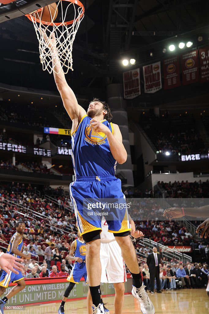 Andrew Bogut #12 of the Golden State Warriors shoots a layup against the Houston Rockets on February 5, 2013 at the Toyota Center in Houston, Texas.