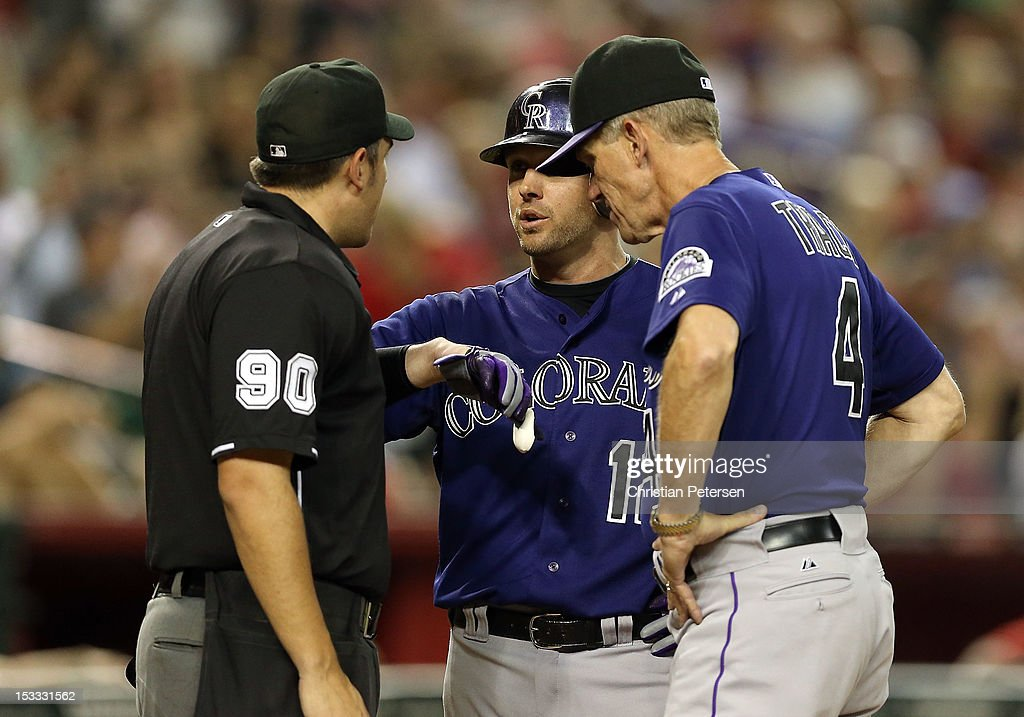 Andrew Brown #12 and manager Jim Tracy of the Colorado Rockies argue with home plate umpire Mark Ripperger that Brown was hit in the hand by a pitch during the eighth inning of the MLB game against the Arizona Diamondbacks at Chase Field on October 3, 2012 in Phoenix, Arizona.