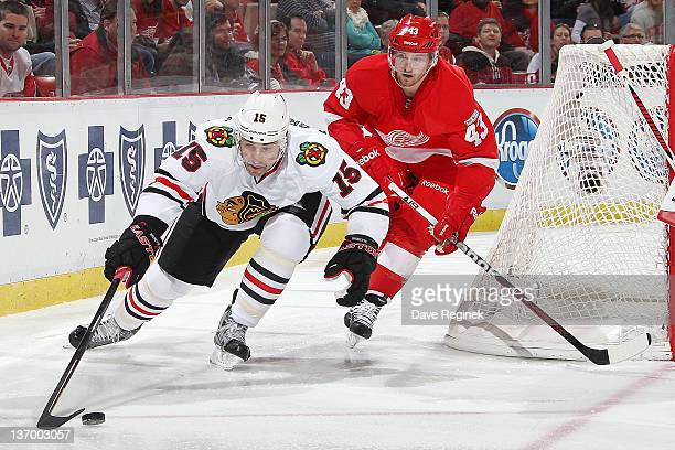 Andrew Brunette of the Chicago Blackhawks controls the puck while Darren Helm of the Detroit Red Wings follows after during an NHL game at Joe Louis...