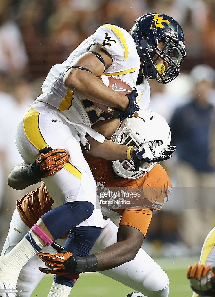 Andrew Buie #13 of the West Virginia Mountaineers is tackled by Steve Edmond #33 of the Texas Longhorns at Darrell K Royal-Texas Memorial Stadium on October 6, 2012 in Austin, Texas.