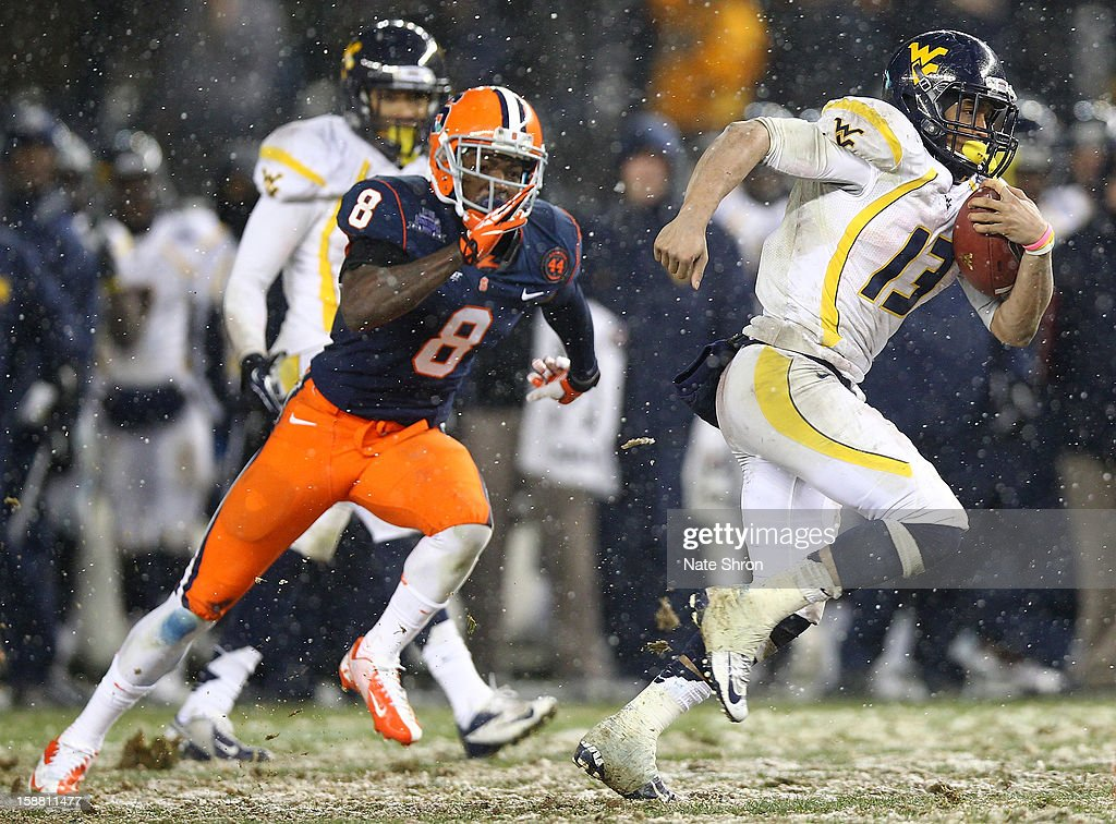 Andrew Buie #13 of the West Virginia Mountaineers runs the ball against Keon Lyn #8 of the Syracuse Orange during the New Era Pinstripe Bowl at Yankee Stadium on December 29, 2012 in the Bronx borough of New York City.