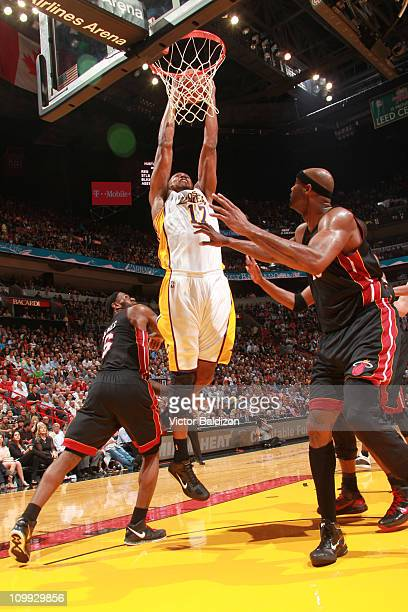 Andrew Bynum of the Los Angeles Lakers dunks against Erick Dampier of the Miami Heat on March 10 2011 at American Airlines Arena in Miami Florida...