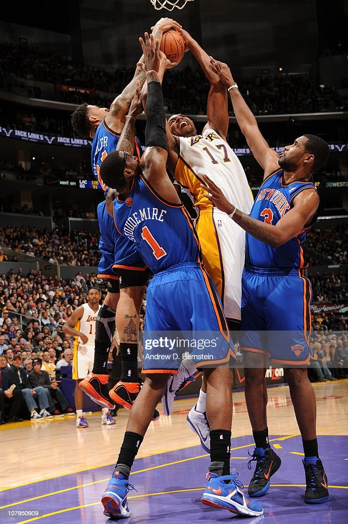 Andrew Bynum of the Los Angeles Lakers is challenged by Wilson Chandler Amar'e Stoudemire and Shawne Williams of the New York Knicks on his way to...