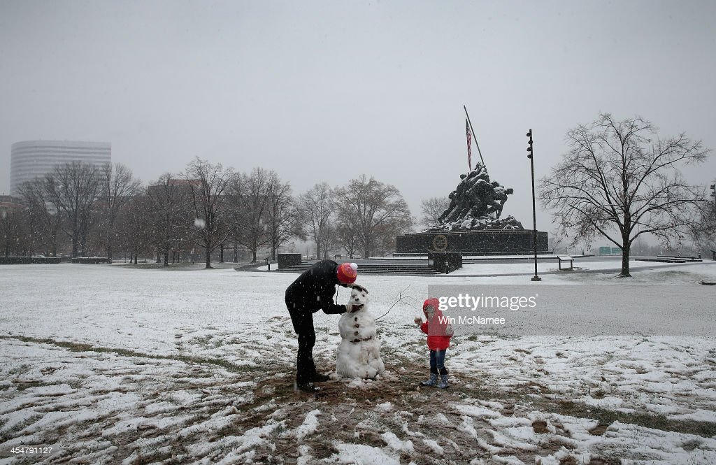 Andrew Carnahan and his daughter Roxanne build a snowman as snow falls during a winter storm at the Marine Corps War Memorial December 10, 2013 in Arlington, Virginia. Forecasts called for significant snowfall in the Washington, DC area as much of the nation reels from severe winter weather.