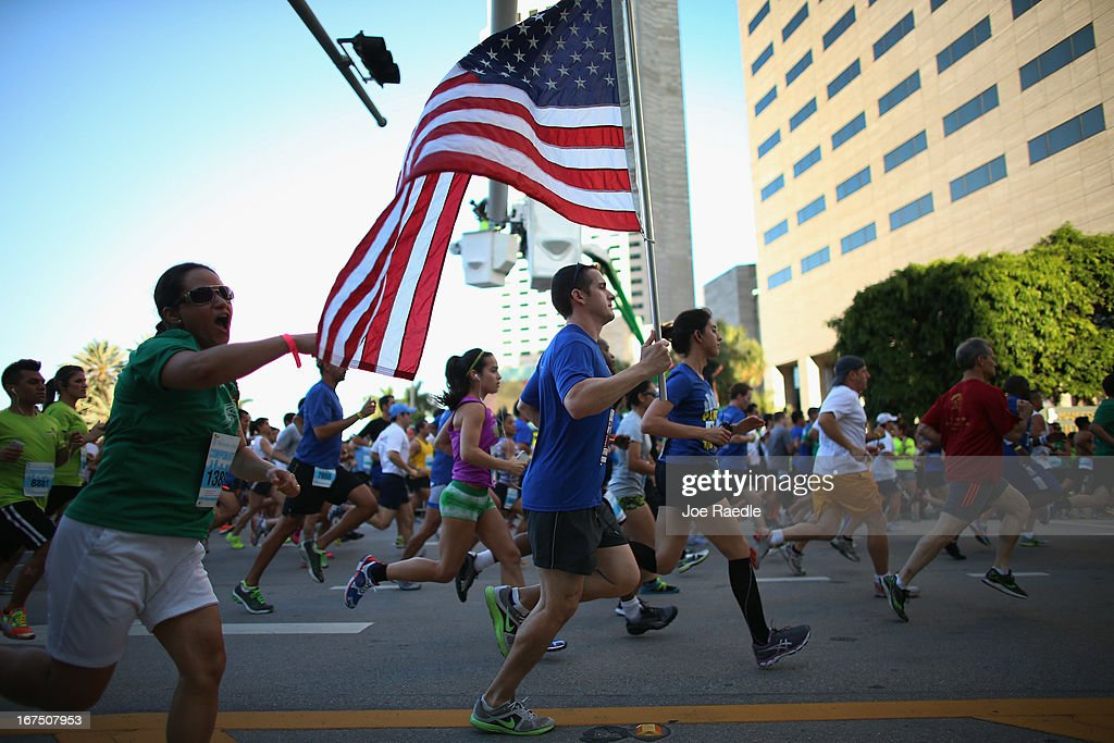 Andrew Carricarte carries an American flag as he and other runners participate in the Mercedes-Benz Corporate Run where security was stepped up after the bombing at the Boston Marathon on April 25, 2013 in Miami, Florida. Carricarte said he was carrying the flag to show that America isn't afraid after the Boston bombing. More than 20,000 people participated in the run.
