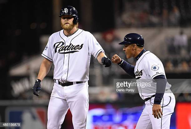 Andrew Cashner of the San Diego Padres is congratulated by Jose Valentin after hitting a single during the third inning of a baseball game against...