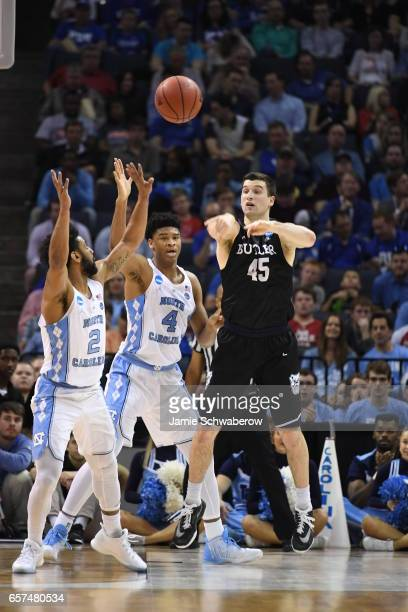 Andrew Chrabascz of Butler University passes the ball against Joel Berry II and Isaiah Hicks of the University of North Carolina during the 2017 NCAA...