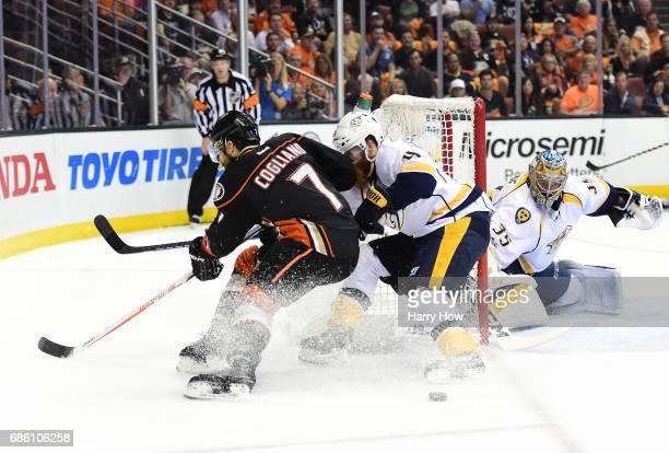 Andrew Cogliano of the Anaheim Ducks and Ryan Ellis of the Nashville Predators tie one another up as goaltender Pekka Rinne of the Nashville...