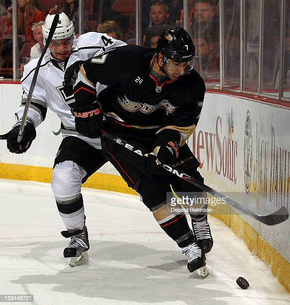 Andrew Cogliano of the Anaheim Ducks controls the puck alongside the boards against Andrei Loktionov of the Los Angeles Kings during the game on...