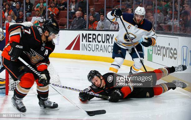 Andrew Cogliano of the Anaheim Ducks gains control of the puck as Rickard Rakell battles against Marco Scandella of the Buffalo Sabres during the...
