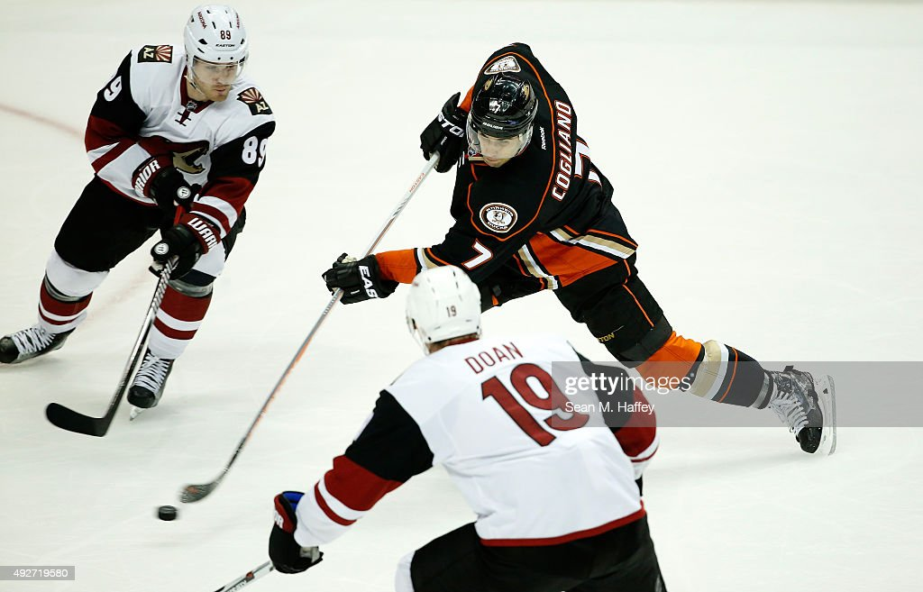 Andrew Cogliano #7 of the Anaheim Ducks shoots the puck as Mikkel Boedker #89 of the Arizona Coyotes, and Shane Doan #19 of the Arizona Coyotes defend during the third period of a game at Honda Center on October 14, 2015 in Anaheim, California.