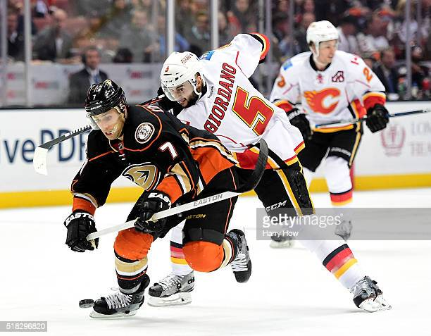Andrew Cogliano of the Anaheim Ducks skates in on goal as he is checked by Mark Giordano of the Calgary Flames for a hooking penalty during the first...