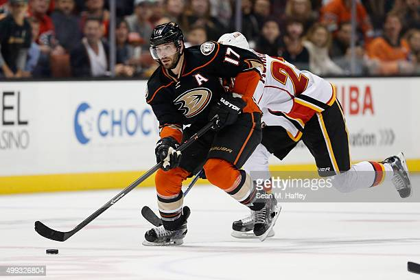 Andrew Cogliano of the Anaheim Ducks skates with the puck away from Sean Monahan of the Calgary Flames during a game at Honda Center on November 24...