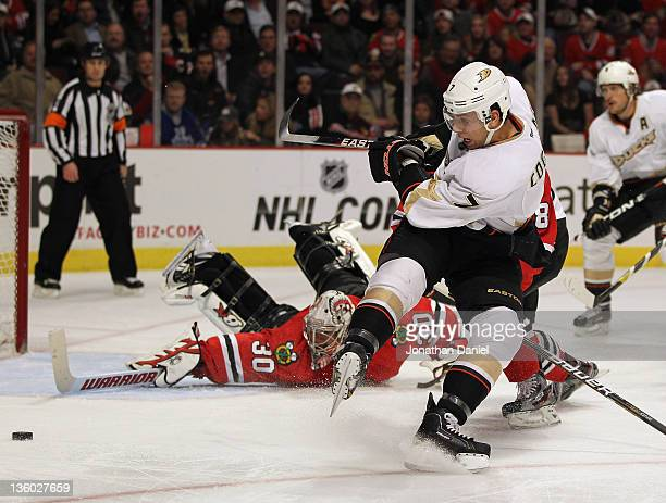 Andrew Cogliano of the Anaheim Ducks tries to get off a shot against Ray Emery of the Chicago Blackhawks after being hooked by Nick Leddy from behind...