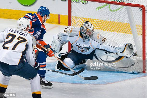 Andrew Cogliano of the Edmonton Oilers tips the puck past Pekka Rinne of the Nashville Predators at Rexall Place on January 23 2011 in Edmonton...