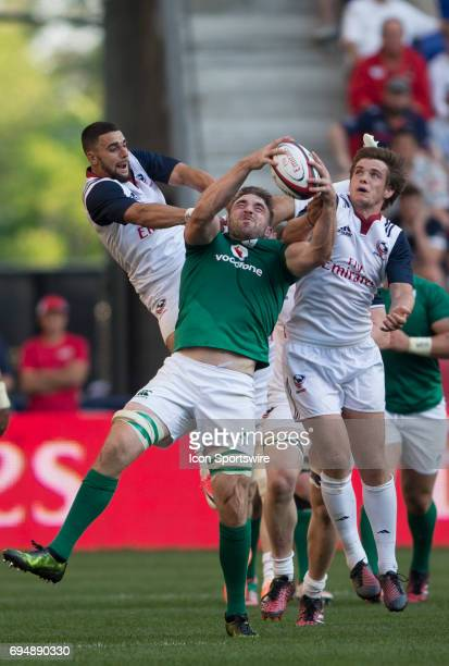 Andrew Conway of Ireland holds onto the ball while tacked by AJ MacGinty and Nate Augspurger of the USA during an international rugby match between...