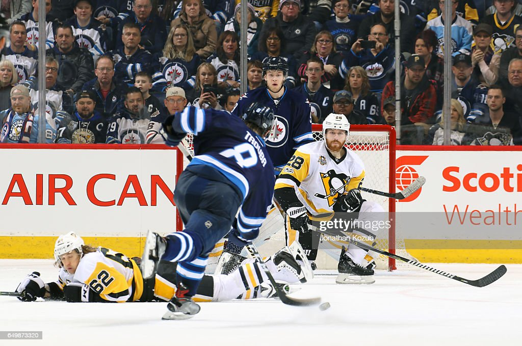 Andrew Copp #9 of the Winnipeg Jets and Ian Cole #28 of the Pittsburgh Penguins watch as Jacob Trouba #8 shoots the puck off the point during third period action at the MTS Centre on March 8, 2017 in Winnipeg, Manitoba, Canada.