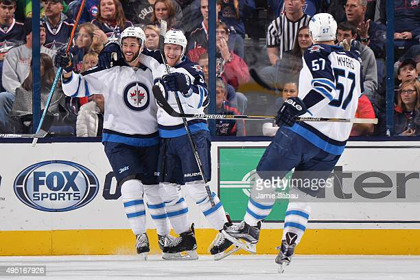 Andrew Copp of the Winnipeg Jets celebrates his first period goal with teammates Anthony Peluso and Tyler Myers of the Winnipeg Jets during a game...