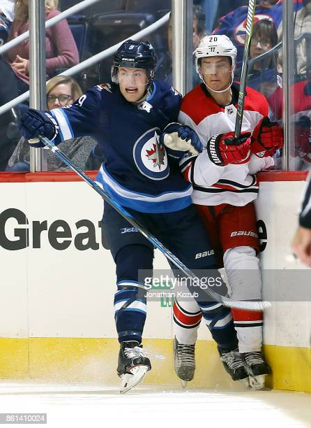 Andrew Copp of the Winnipeg Jets checks Sebastian Aho of the Carolina Hurricanes along the boards during second period action at the Bell MTS Place...