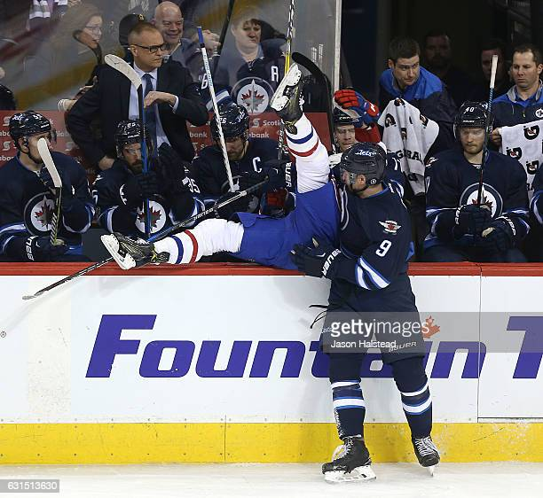 Andrew Copp of the Winnipeg Jets dumps Daniel Carr of the Montreal Canadiens into the Jets' bench during NHL action on January 11 2017 at the MTS...