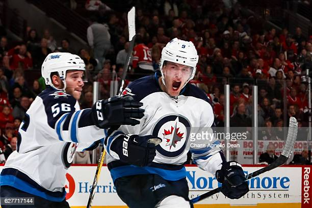 Andrew Copp of the Winnipeg Jets reacts with teammate Marko Dano after scoring the game winning goal against the Chicago Blackhawks in the third...