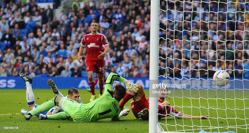 Andrew Crofts of Brighton dives low to head into the net past goalkeeper Karl Darlow of Nottingham Forest during the Sky Bet Championship match between Brighton & Hove Albion and Nottingham Forest at Amex Stadium on October 5, 2013 in Brighton, England.
