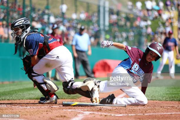 Andrew Cutler of the New England team from Connecticut slides into home against JR Osmond of the MidAtlantic team from New Jersey during Game 2 of...