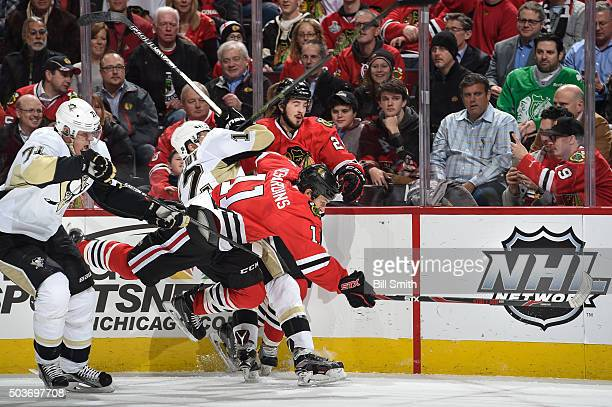 Andrew Desjardins and Phillip Danault of the Chicago Blackhawks battle for the puck against Evgeni Malkin and Ben Lovejoy of the Pittsburgh Penguins...