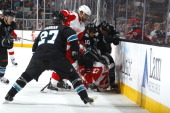 Andrew Desjardins and Tyler Kennedy of the San Jose Sharks battle for the puck against Kyle Quincey of the Detroit Red Wings at SAP Center on January...
