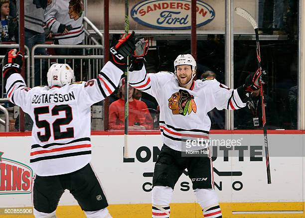 Andrew Desjardins of the Chicago Blackhawks celebrates with teammate Erik Gustafsson after his third period goal against the Arizona Coyotes at Gila...